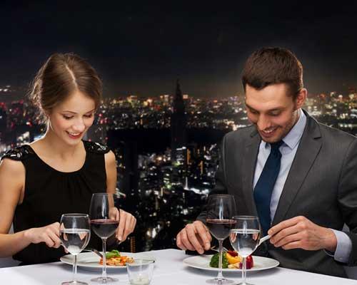 夜景を背景に食事するカップル
