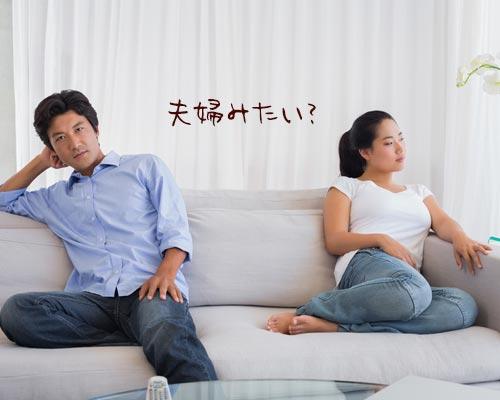 互いに顔を反らしてソファーに座るカップル
