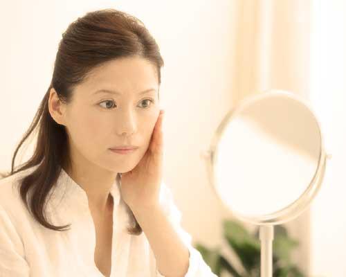 鏡に顔を映して頬を触る女性