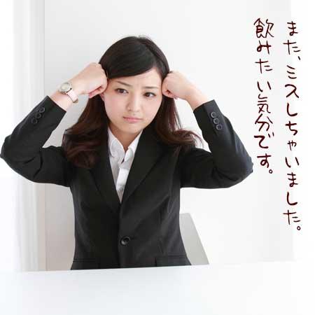 職場のデスクで頭を押さえている女性