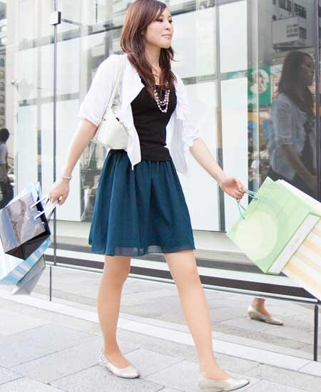 ショッピングバッグを数個両手にして歩く女性