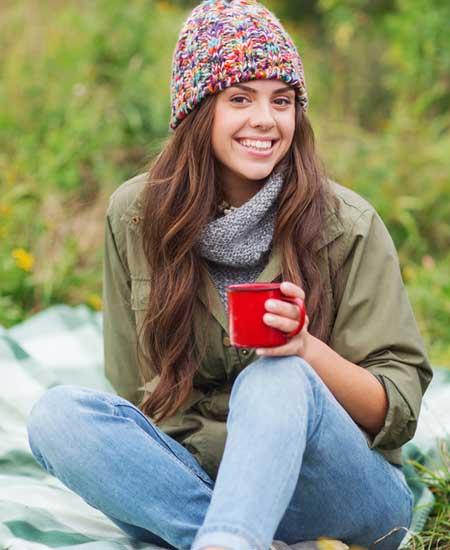 野原でシートに座る笑顔の女性