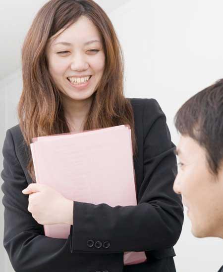 職場で笑顔で話す女性