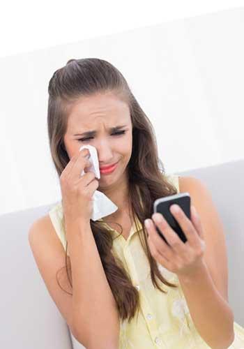 泣きながらメールを撃つ女性