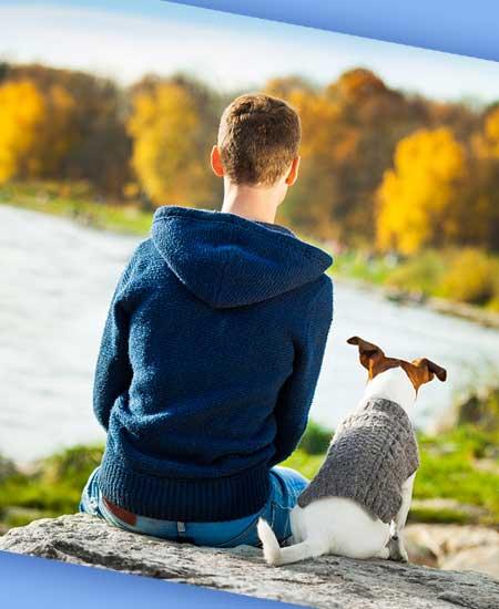 犬と一緒に湖の見える場所に座る男性