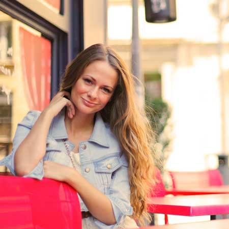 カフェの戸外席で一人で微笑む女性