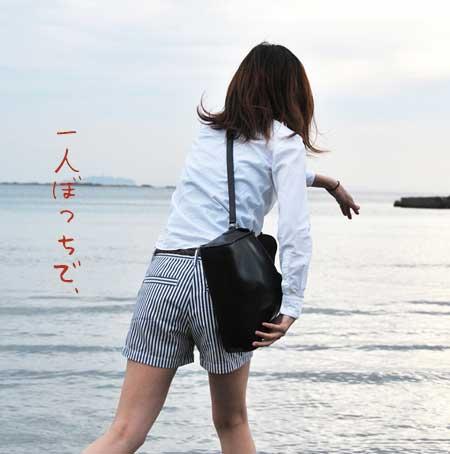 海に向かって石を投げる女性