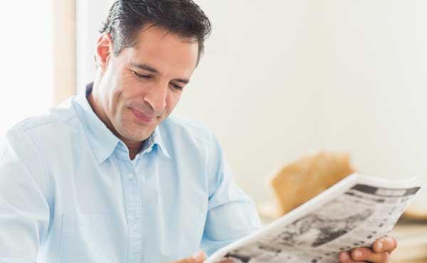 新聞を読む中年男性