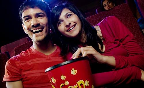 映画館で恋人にもたれかかる女性