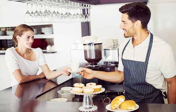 カフェでコーヒーを受け取る女性
