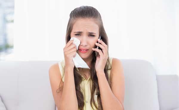 電話をしながら涙を流す泣いている女性