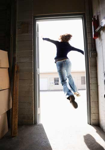 ドアを開けて玄関を飛び出す女性
