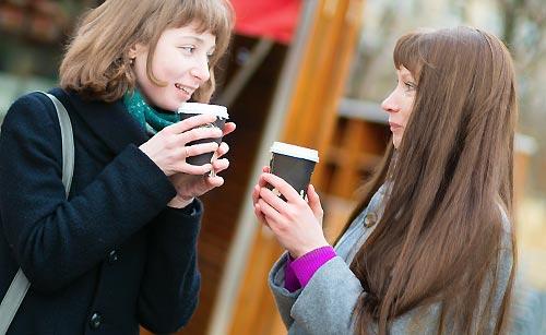 コーヒーを飲み会話をする女の子