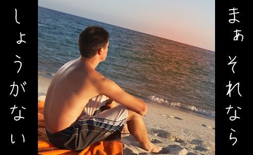 夕日の砂浜で何かを思う男性