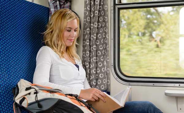 荷物と電車に乗る女性