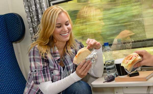 電車でサンドウィッチを食べる女性