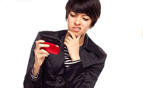 ぶっきらぼうに携帯を持つ女性