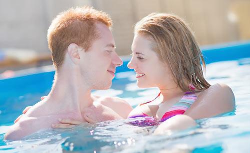 プールで泳ぐカップル