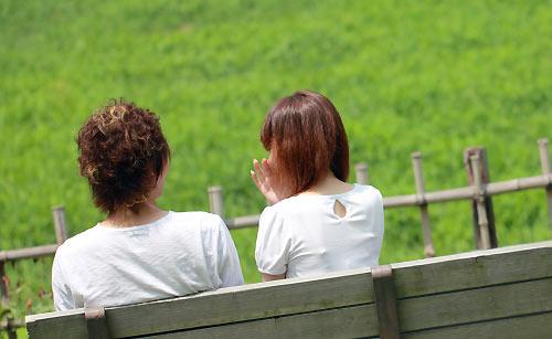 公園のベンチで会話するカップル