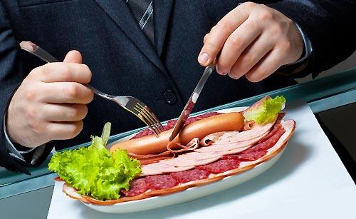ナイフとフォークで食事をする男