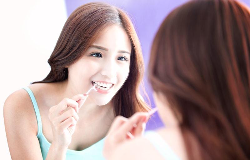 デンタルフロスで歯をケアする女