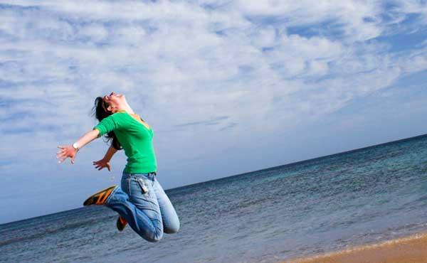 アクティブに海でジャンプする女性