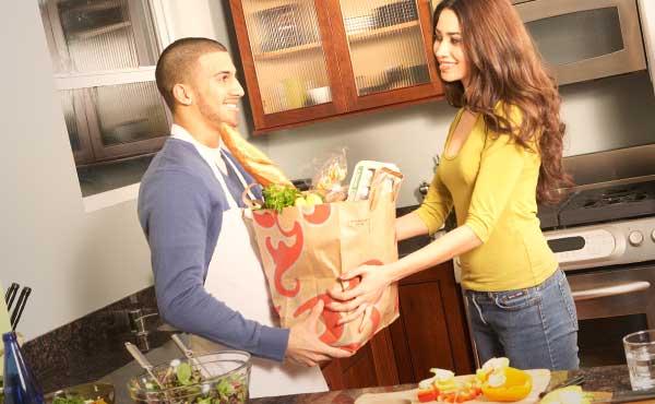 食材をもって料理を始めるカップル