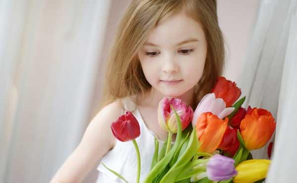 花の香りをかいでリラックスする女性