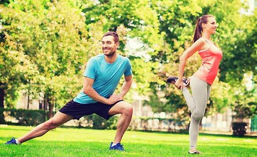 公園で準備運動をするカップル