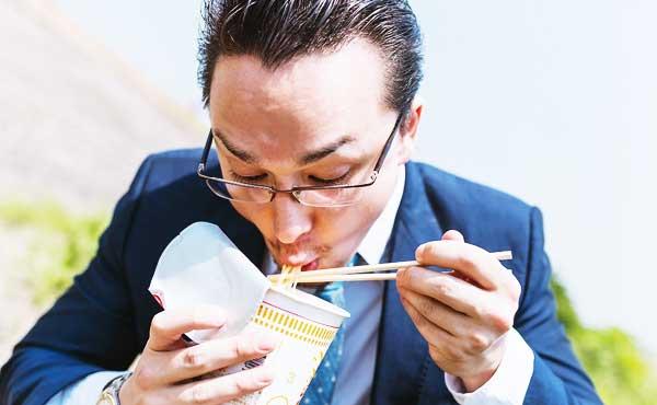 カップメンを食べる男性