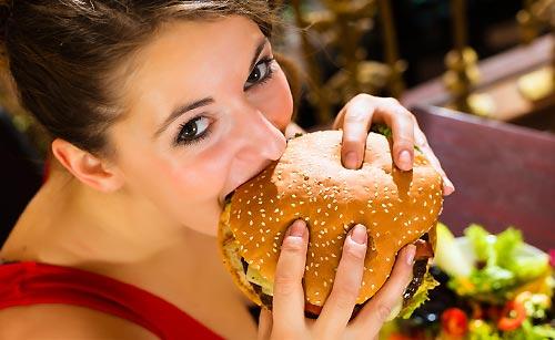 大きいハンバーガーをたべる女性