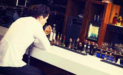 酒を飲み落ち込む男
