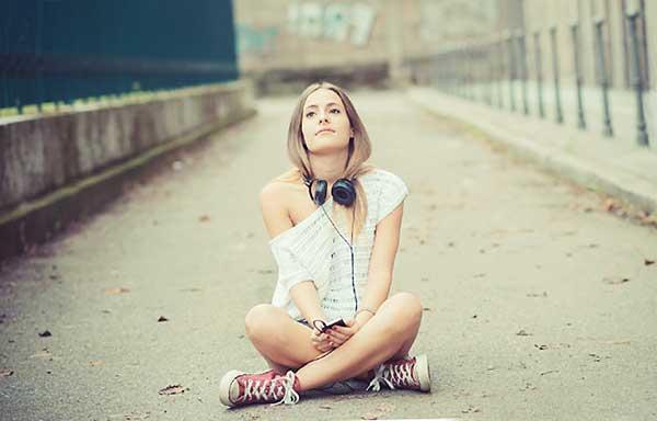音楽を聴き空を見上げる女性