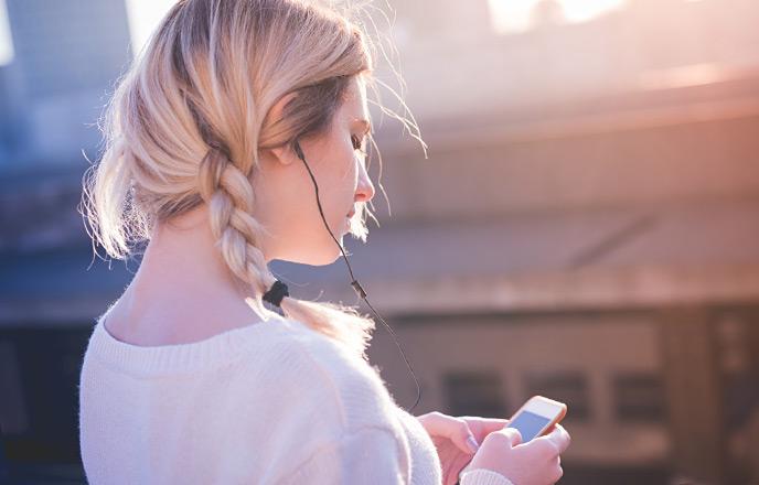 夕日の下で音楽を聴く女性