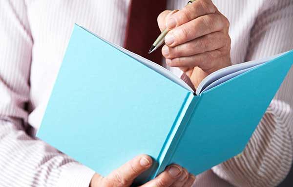手帳に予定を書くビジネスマン