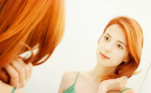 鏡で髪を整える女性
