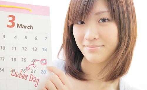 カレンダーを指さす女性