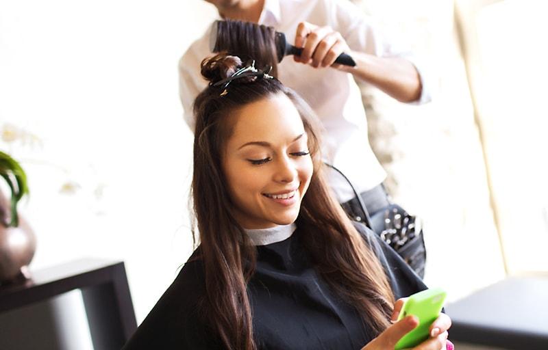 美容院でスマホを見る女性