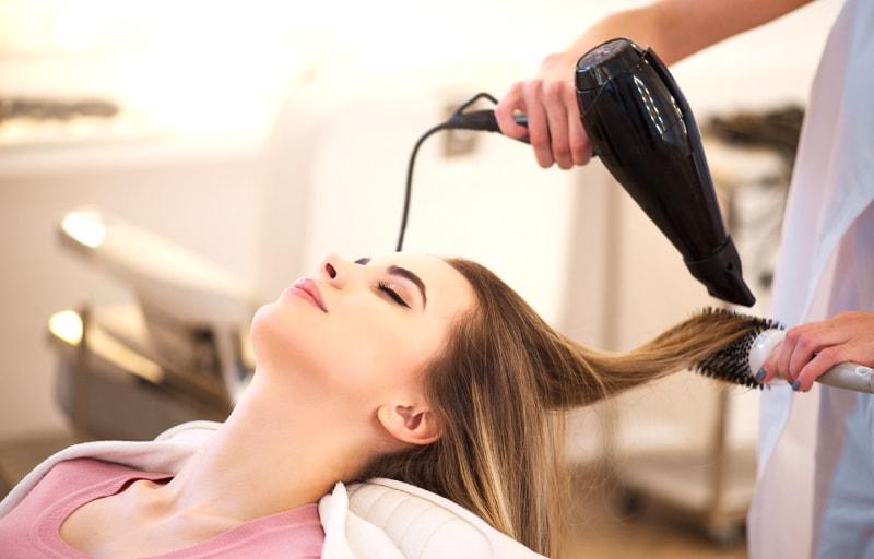 美容院で髪を乾かす女性