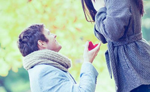 ひざまずいて女性にプレゼントを渡す男性