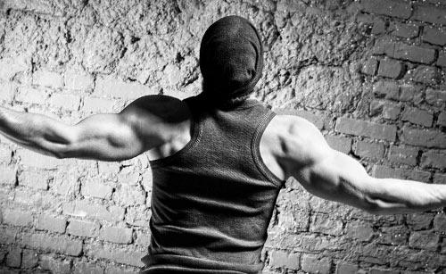筋肉がアピールする後ろ向きの男性