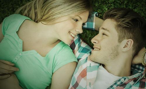 寝ながら笑顔で寄り添うカップル