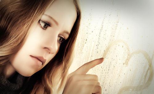 寂しそうに窓にハートを描く女性
