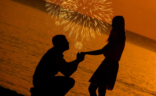 夕暮れの海で彼女の手を握る男性