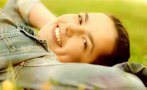 草原で笑顔で寝る女性