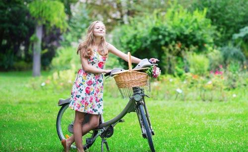 自転車を持ってゆっくり歩く女子