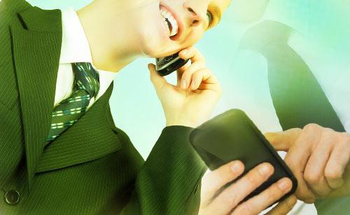 2台のスマートフォンを使うスーツの男性