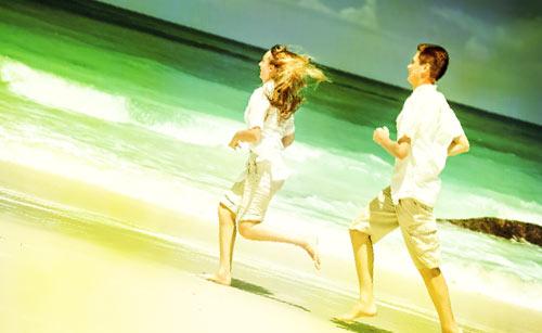 昼間に砂浜を走るカップル