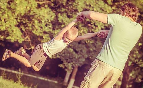 子供の遊び相手をする父親