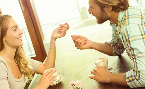 コーヒーを飲みながら話合うカップル